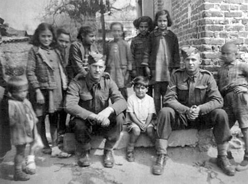 Allan Robinson (right) and another New Zealand soldier surrounded by children in Greece, circa March-April 1941.